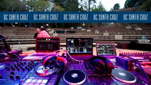 Photo of DJ equipment on the stage in The Quarry with blue logo stripe across the top